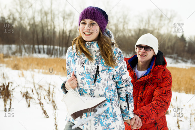 Caucasian couple carrying ice skates in snowy field