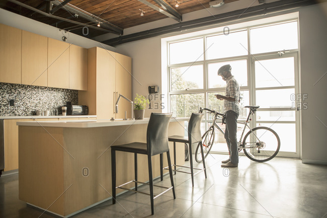 Black businessman with bicycle using cell phone in office kitchen