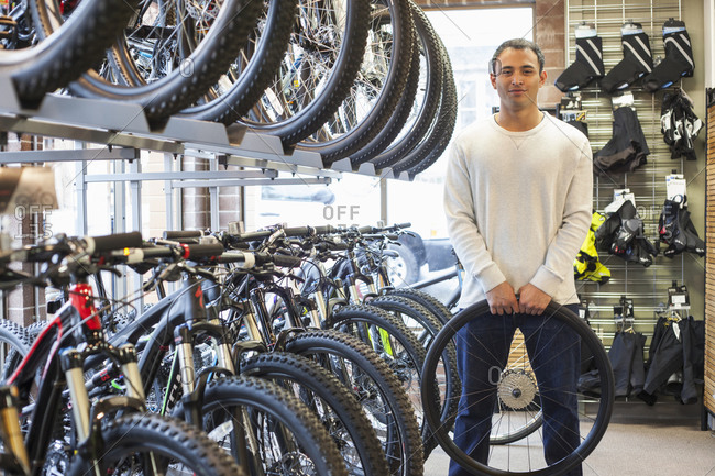 Mixed race man holding wheel in bicycle shop