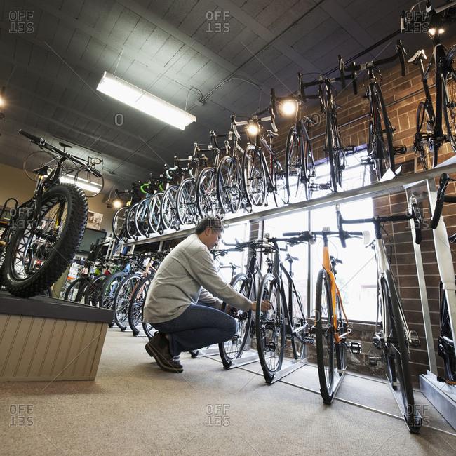 Pacific Islander man examining bicycles in bicycle shop