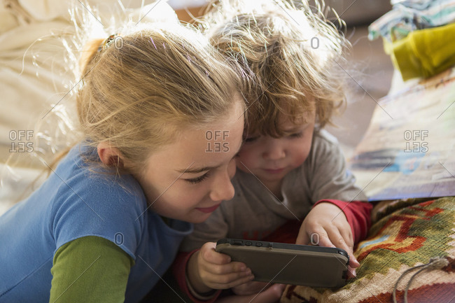 Caucasian brother and sister using cell phone on sofa