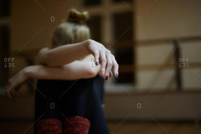 Fatigued Caucasian dancer sitting on studio floor