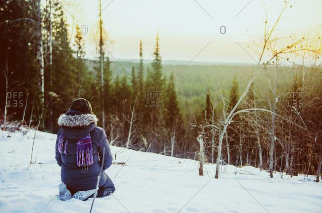 Caucasian hiker admiring scenic view from snowy hillside