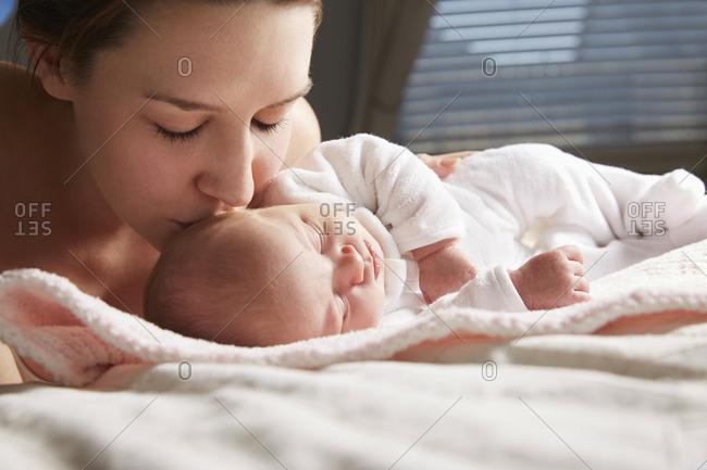 Mother kissing newborn baby on blanket