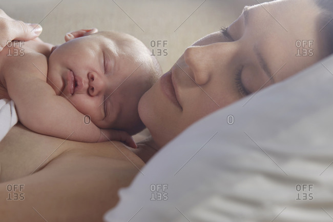 Mother sleeping with newborn baby on bed