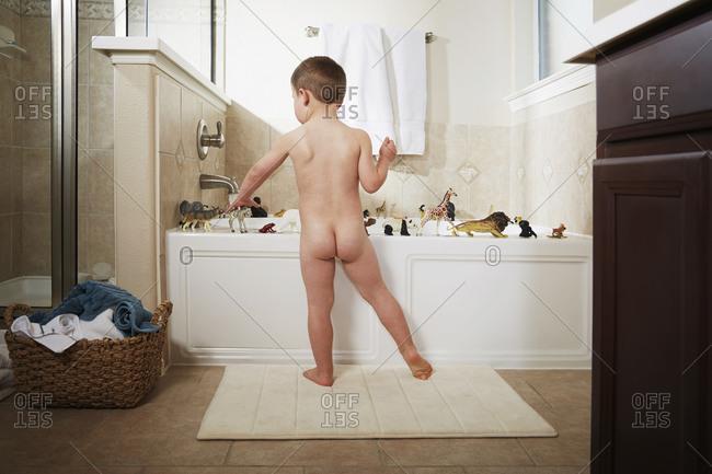 Nude Caucasian boy playing in bathtub