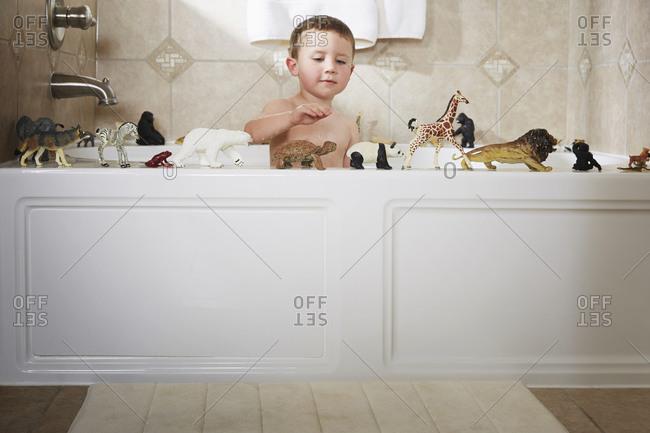 Caucasian boy playing in bathtub