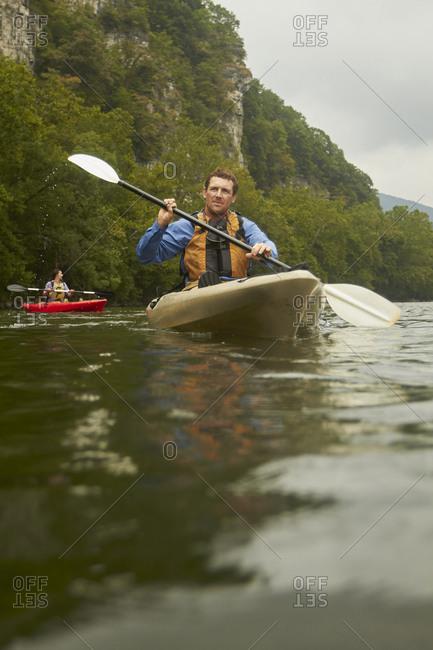 Caucasian man paddling kayak on remote river