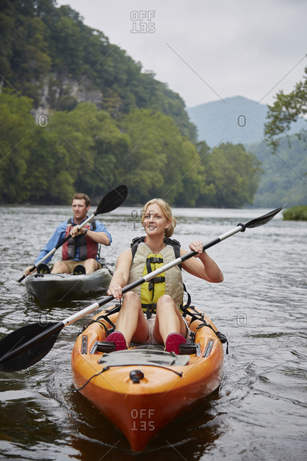 Caucasian couple paddling kayaks in remote river