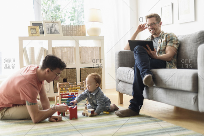 Caucasian gay fathers and baby relaxing in living room