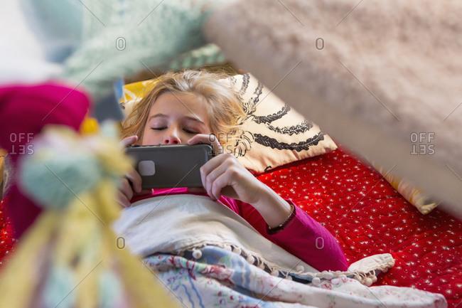 Caucasian girl using cell phone in blanket fort