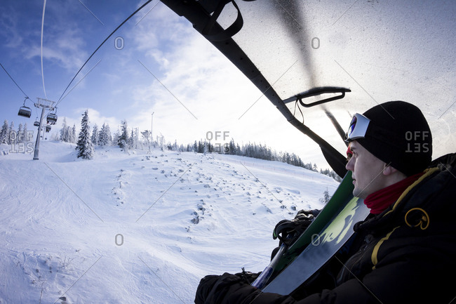 Caucasian snowboarder riding chair lift over snowy slopes