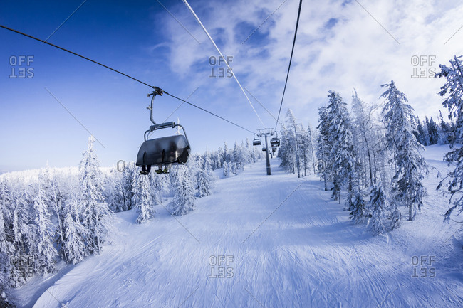 Chair lift gondolas over snowy slopes