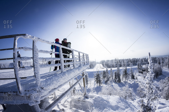 Caucasian snowboarders standing on snowy platform