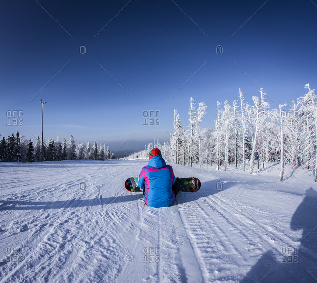 Caucasian snowboarder sitting on snowy slope