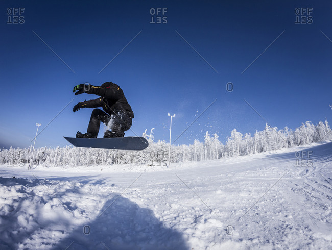 Caucasian snowboarder jumping on snowy slope