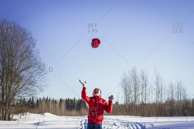 Caucasian girl throwing hat in snowy field