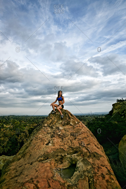 Vietnamese woman sitting on rocky hilltop