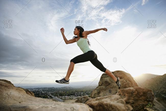 Vietnamese woman leaping on rocky hillside