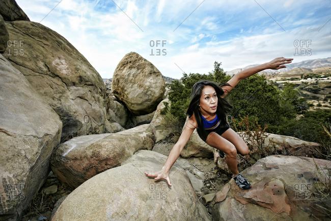 Vietnamese woman climbing on rocky hillside