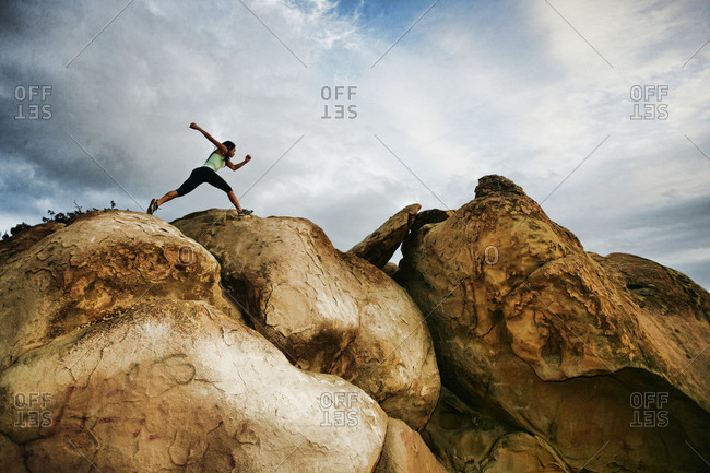 Vietnamese woman running on rocky hilltop