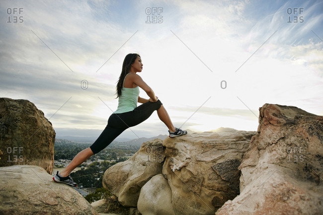 Vietnamese woman stretching on rocky hilltop