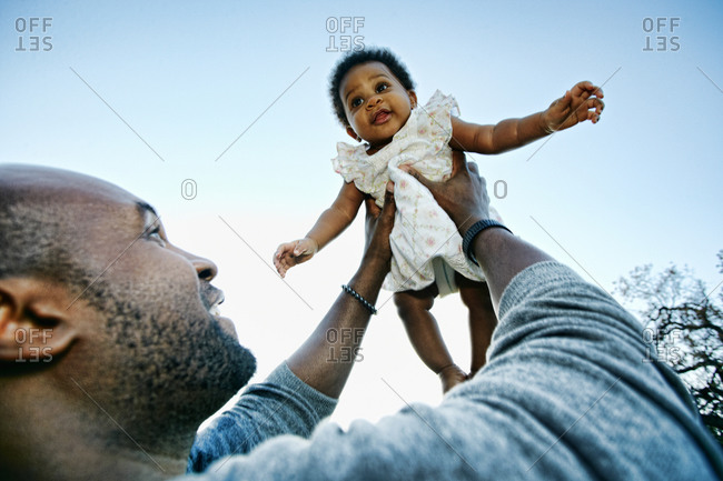 Black father holding baby daughter under blue sky