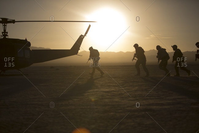 Soldiers boarding helicopter in remote desert