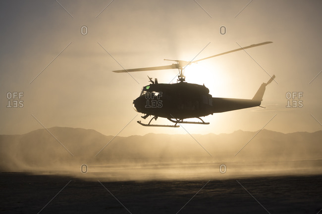 Silhouette of helicopter flying over remote landscape