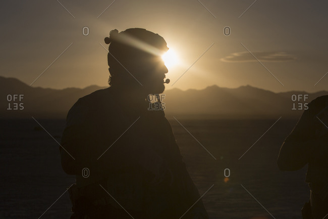 Silhouette of soldier standing in desert landscape