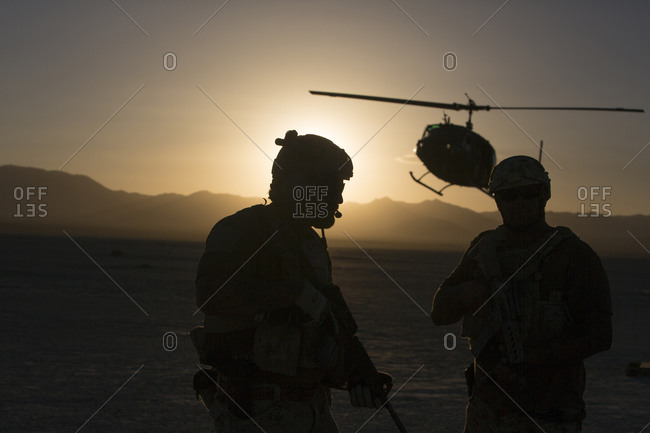 Silhouette of soldiers and helicopter in desert landscape