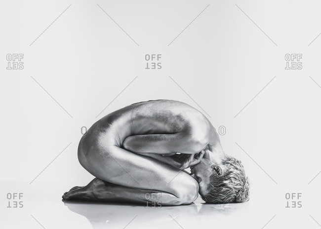 Nude Caucasian woman with silver body paint in fetal position