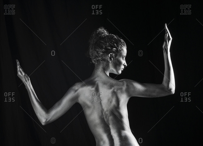 Rear view of nude Caucasian woman with silver body paint