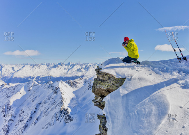 Photographer photographing from snowy mountaintop