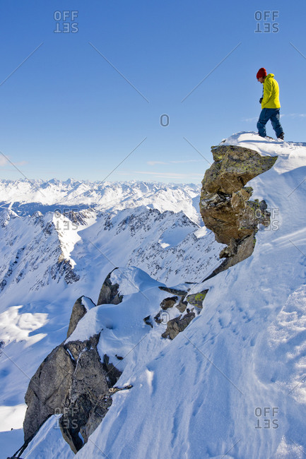 Hiker admiring scenic view from snowy mountaintop