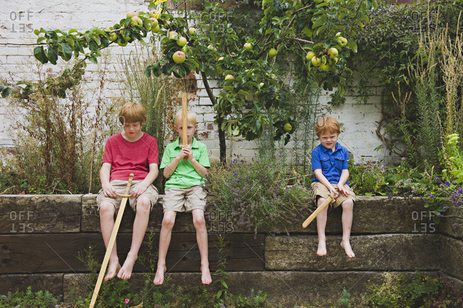 Caucasian brothers holding toy swords in backyard