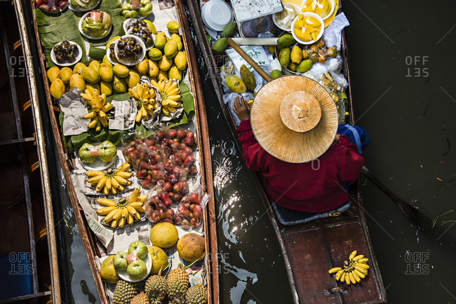 Damnoen Saduak, Thailand - February 13, 2015: High angle view of merchant selling fruit in canoe