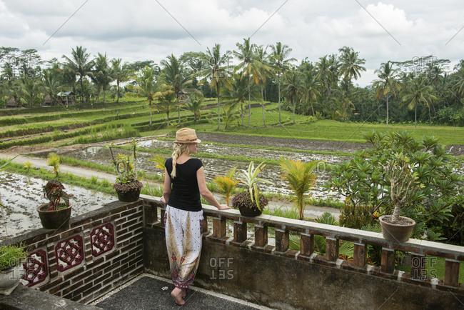 Caucasian woman admiring rural farm fields from rooftop