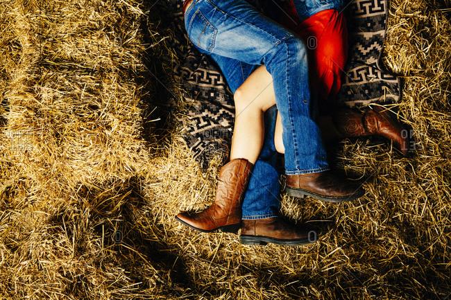 Caucasian couple laying on haystacks
