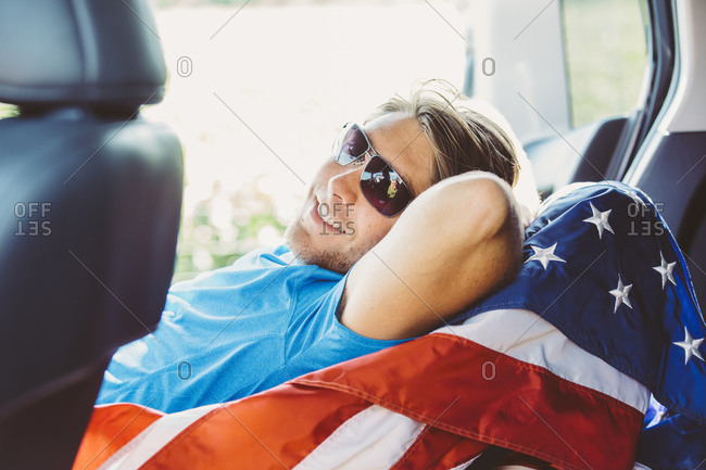 Caucasian man laying on American flag in car
