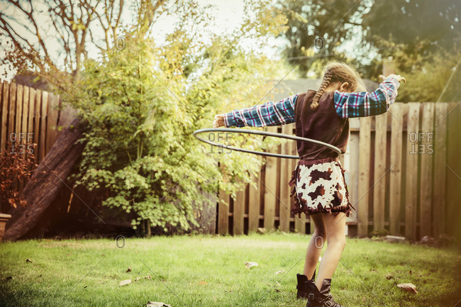Mixed race girl in cowboy costume spinning plastic hoop in backyard