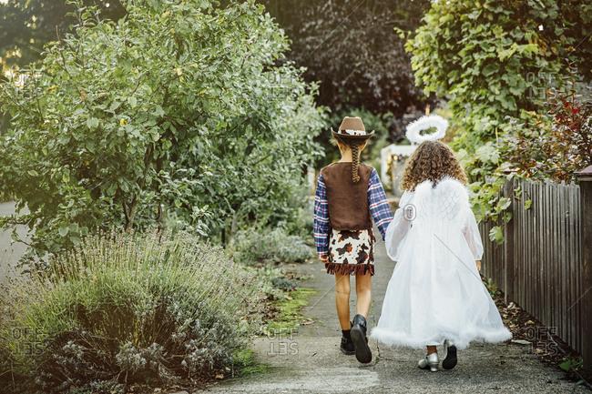 Sisters wearing Halloween costumes on sidewalk