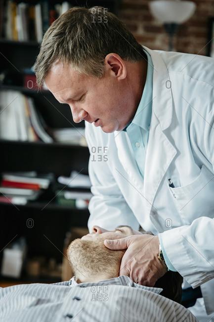 Caucasian doctor adjusting neck of patient