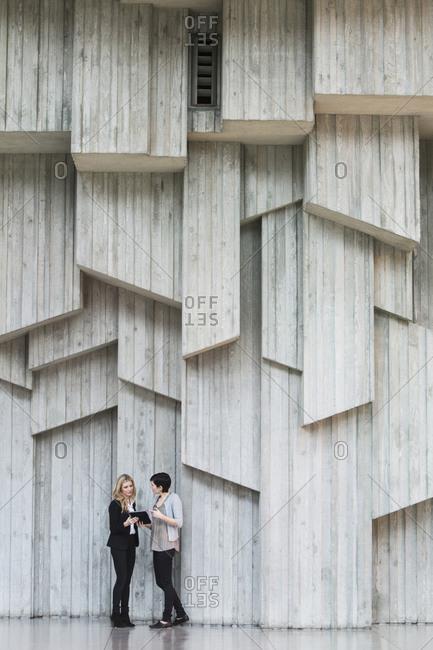 Caucasian businesswomen talking under office wall art