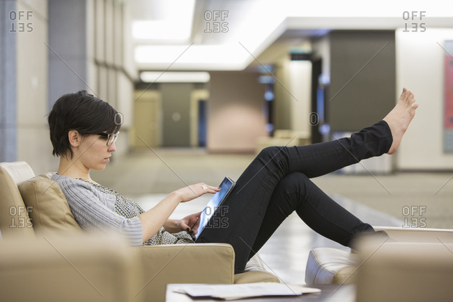 Caucasian businesswoman relaxing barefoot in office lobby