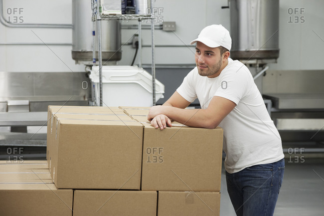 Caucasian man leaning on cardboard boxes in factory