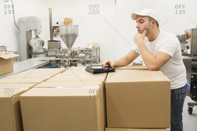 Caucasian worker using digital tablet on cardboard boxes in factory