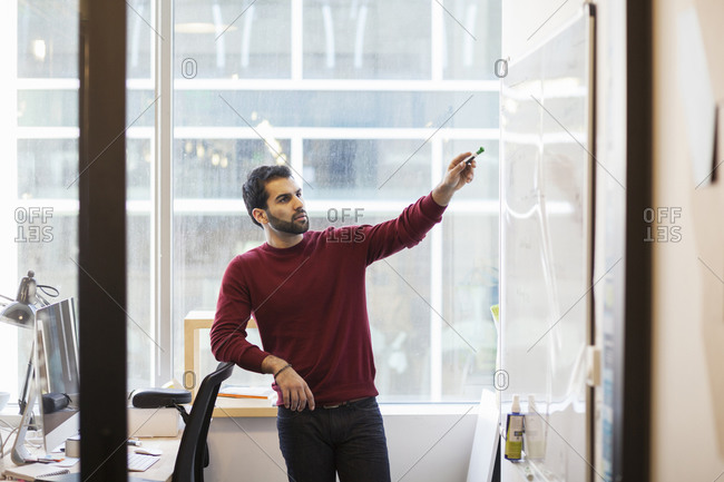 Mixed race businessman pointing to whiteboard in office