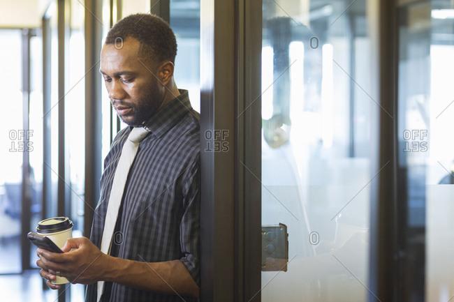 Black businessman using cell phone in office doorway