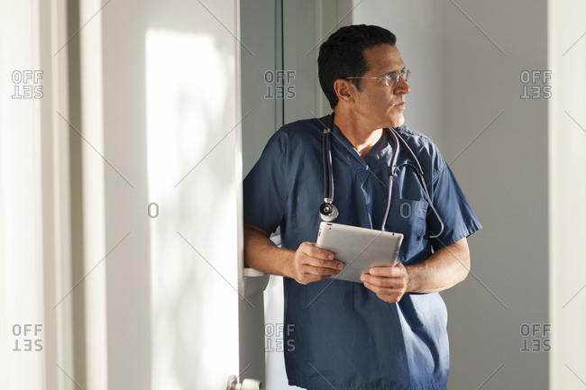 Hispanic doctor using digital tablet in hallway